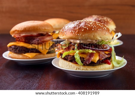 Group of burgers on dish with home baked buns - stock photo