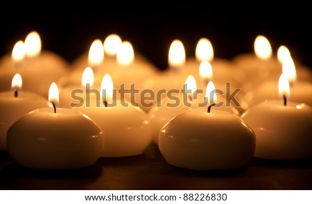Group of burning candles at a black background with selective focus - stock photo