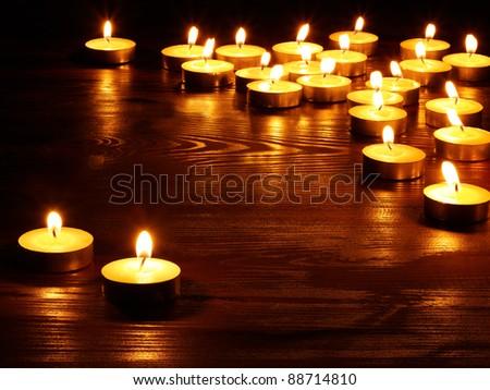 Group of burning candles on  black background. - stock photo