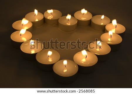 Group of burning candles placed in form of heart. - stock photo