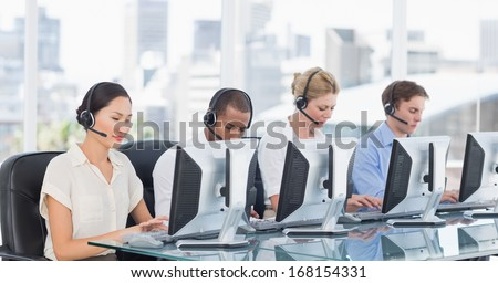Group of business colleagues with headsets using computers at office desk - stock photo