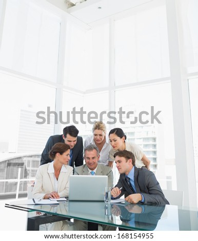 Group of business colleagues with laptop at office desk - stock photo