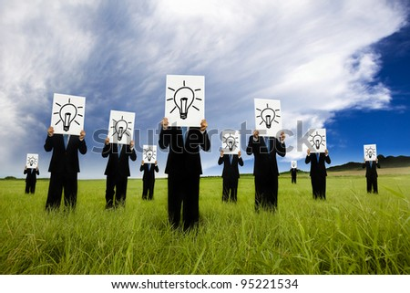 group of business man holding bulb symbol. business idea and solution concept - stock photo