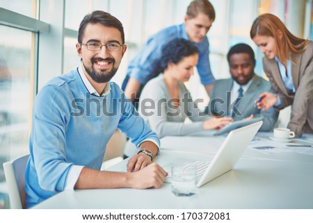Group of business partners discussing ideas with their leader on foreground - stock photo