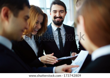 Group of business partners discussing papers and explaining ideas at meeting with focus on happy man looking at camera - stock photo