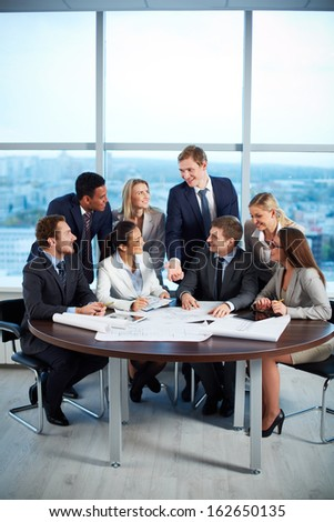 Group of business partners discussing their ideas at meeting - stock photo