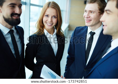 Group of business partners explaining ideas at meeting, happy woman looking at camera - stock photo