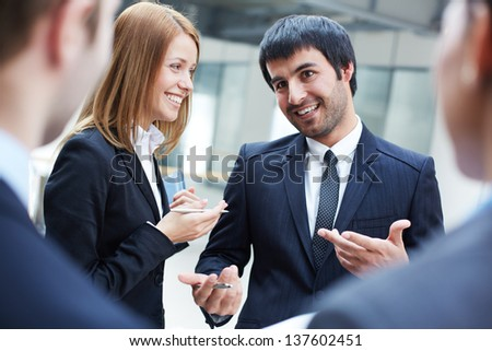 Group of business partners interacting at meeting, focus on smart man - stock photo