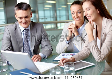 Group of business partners interacting at meeting while looking at laptop display - stock photo