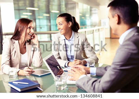 Group of business partners interacting at meeting with focus on happy young women - stock photo