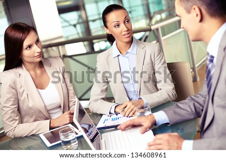 Group of business partners interacting at meeting with focus on two young women - stock photo