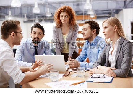 Group of business partners listening to colleague at meeting - stock photo