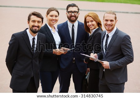 Group of business partners looking at camera outdoors - stock photo