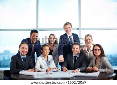 Group of business partners looking at camera with smiles in office