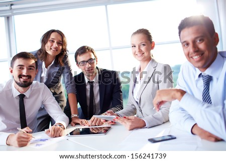 Group of business partners looking at camera with smiles while working in office - stock photo