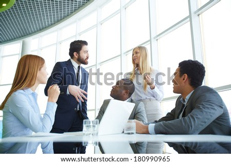 Group of business partners looking at their boss explaining his idea to employee