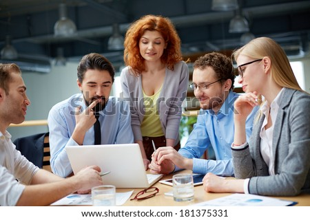 Group of business partners looking attentively at data in laptop at meeting - stock photo