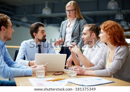 Group of business partners sharing ideas upon project at meeting - stock photo