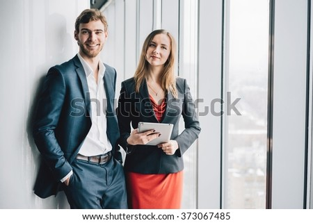 Group of business people, a man in a suit and a woman in a red dress and jacket, holding a tablet, winter city landscape outside the window on the background - stock photo