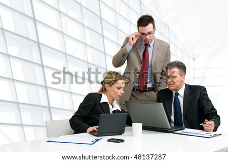 Group of business people analyzing and discussing during a working meeting in a modern office - stock photo
