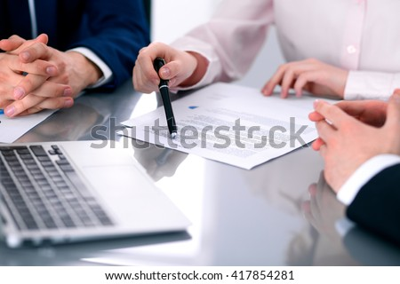 Group of business people and lawyers discussing contract papers sitting at the table, close up - stock photo