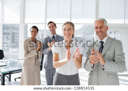 Group of business people applauding together during a meeting - stock photo