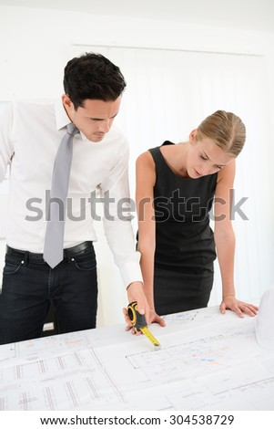 group of business people architect man and woman studying blueprint in office desk - stock photo