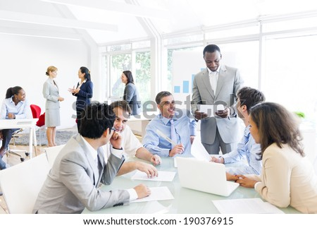 Group of business people around the conference table talking to one another. - stock photo
