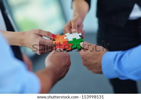 Group of business people assembling jigsaw puzzle and represent team support and help concept - stock photo