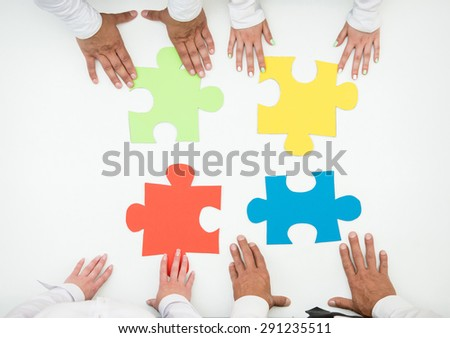 Group of business people assembling jigsaw puzzle and represent team support and help concept. Close-up. - stock photo