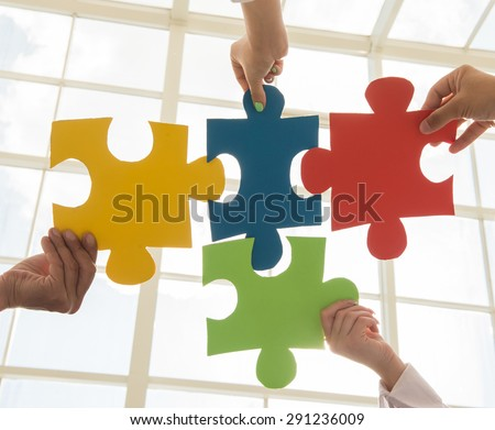 Group of business people assembling jigsaw puzzle and represent team support and help concept. - stock photo