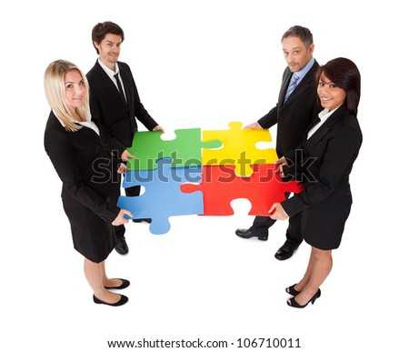Group of business people assembling jigsaw puzzle. Isolated on white - stock photo