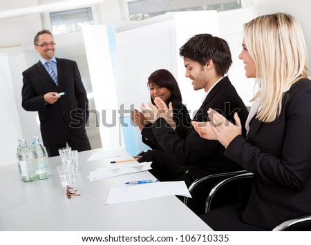 Group of business people at presentation applauding to the lecturer