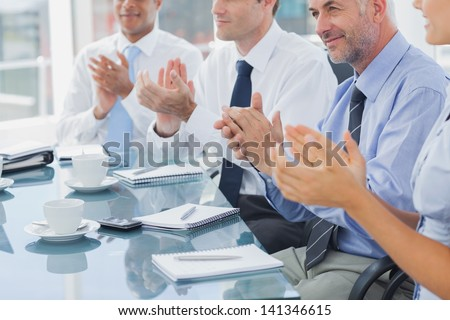 Group of business people clapping together during a meeting - stock photo