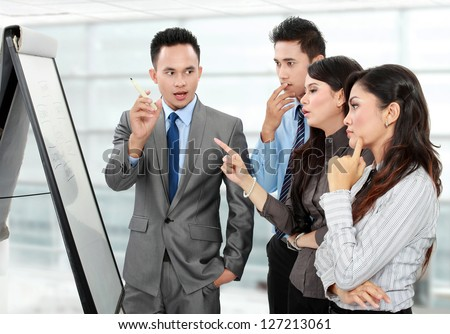Group of business people discussing and looking at whiteboard in the office - stock photo