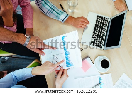 Group of business people discussing graphs sitting at the table. - stock photo