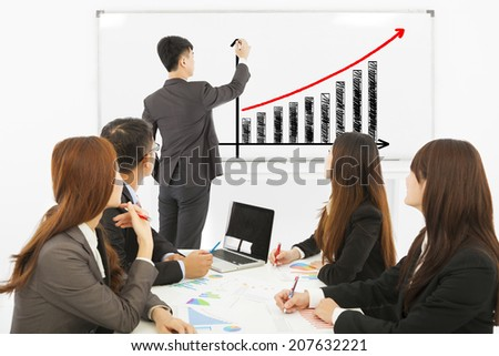 group of business people discussing sales on whiteboard - stock photo
