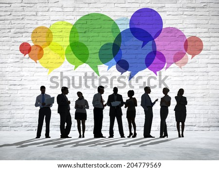 Group of business people discussing with colorful speech bubbles above them. - stock photo