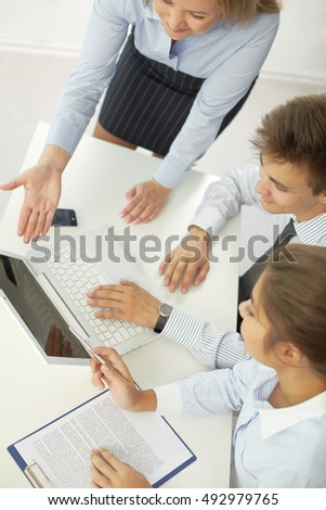 Group of business people doing presentation on laptop together