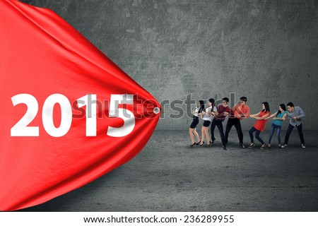 Group of business people drag number 2015, symbolizing a struggle for progress - stock photo