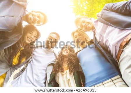 Group of business people embraced in a circle, looking down at camera. They all are young, smiling and wearing smart casual clothes. Mixed race group. Teamwork and business concepts. - stock photo