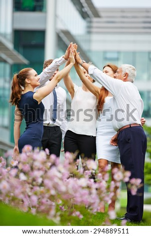 Group of business people giving high five outdoors in front of the office - stock photo