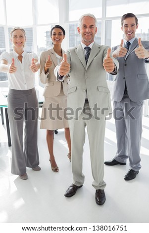 Group of business people giving thumbs up in the meeting room