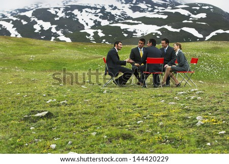 Group of business people having conference in mountain field - stock photo