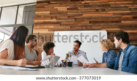 Group of business people having meeting in a board room in an office. Creative team sitting at the table discussing new strategy of their company. - stock photo
