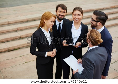 Group of business people having meeting outside, man and woman looking at camera - stock photo
