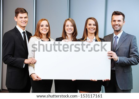 Group of business people holding billboard in the office - stock photo