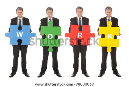 Group of business people holding jigsaw puzzle. Isolated on white - stock photo