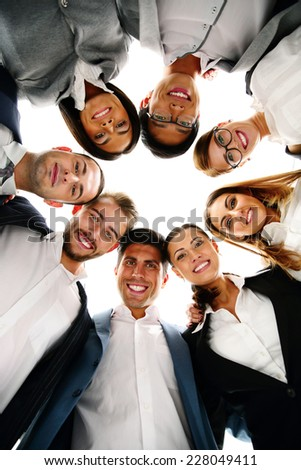 Group of business people in a circle looking down