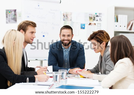 Group of business people in a meeting seated grouped around a table having a discussion with focus to a smiling man at the head of the table - stock photo